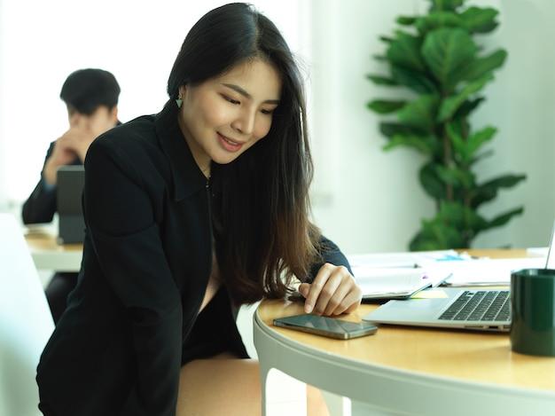 미소하고 사무실 방에 사무실 책상에 스마트 폰을 사용하는 사업가의 초상화