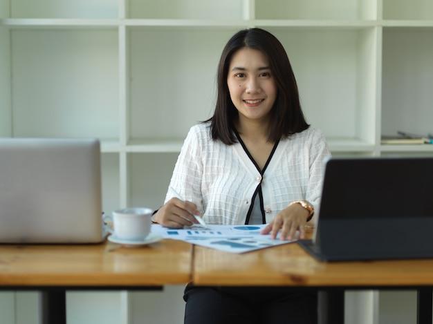 Портрет деловой женщины, улыбаясь в камеру, читая документы в офисной комнате