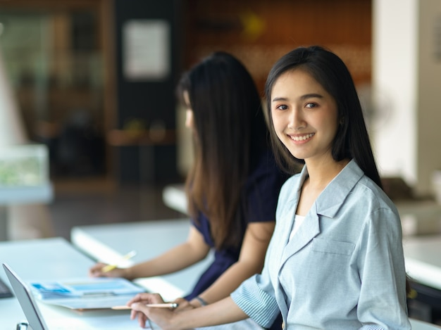 会議室で彼女の同僚の隣に座っている間カメラに微笑んでいる実業家の肖像画