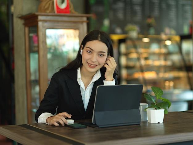 Портрет деловой женщины, улыбаясь в камеру во время перерыва со смартфоном в кафе