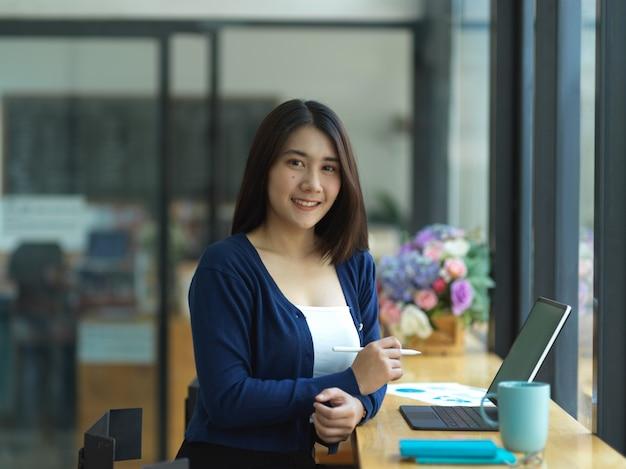 Портрет деловой женщины, улыбаясь в камеру, работая с планшетом и канцелярскими принадлежностями в кафе