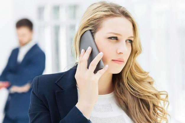 Портрет бизнесвумен, разговаривает по телефону в офисе