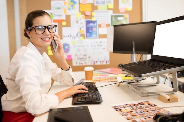 컴퓨터 키보드에 입력하는 동안 휴대 전화를 사용하는 사업가의 초상화