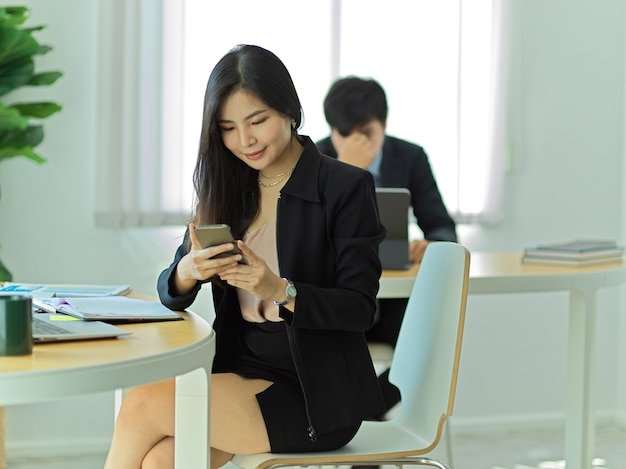 사무실 방에서 작업 공간에 앉아있는 동안 휴식을 취하기 위해 스마트 폰을 사용하는 사업가의 초상화