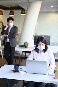 Портрет деловой женщины в защитной маске, работающей на ноутбуке, и ее коллега, говорящая по мобильному телефону в фоновом режиме.