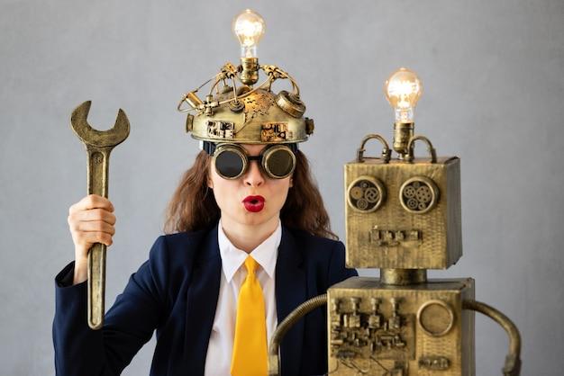 Портрет деловой женщины с роботом против серой бетонной стены
