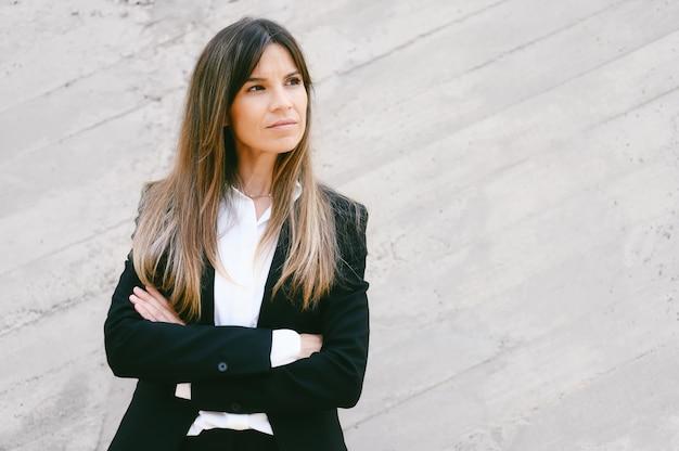 Портрет деловой женщины с серьезным выражением лица, стоящей со скрещенными руками