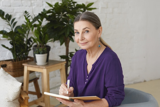 카피 북에 쓰는 보라색 셔츠에 바쁜 현대 50 세 중간 나이 든 여자의 초상화, 계획을 세우고, 긍정적 인 친절한 미소로 찾고, 녹색 식물로 둘러싸인 의자에 앉아