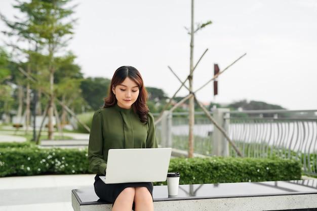 ビジネスパークに座り、モバイルでテキストを書きながらノートパソコンを使う、忙しい営業の女性のポートレート。オンラインで働く実業家。