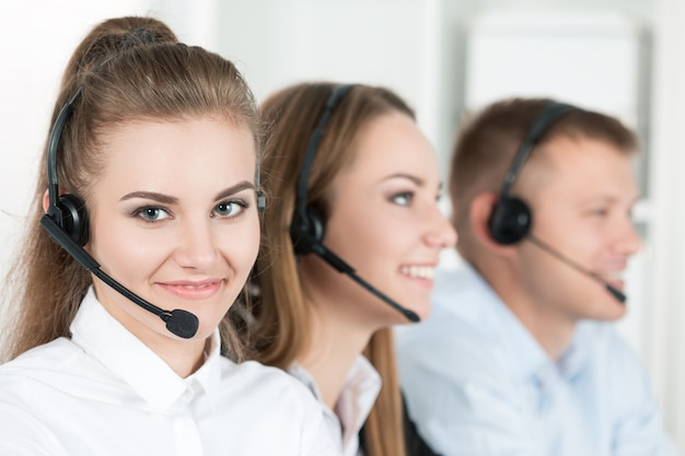彼女のチームを伴うコールセンターの労働者の肖像画。職場での顧客サポートオペレーターの笑顔。ヘルプとサポートのコンセプト
