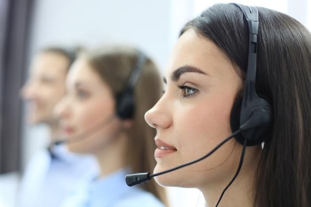 Портрет работника call-центра в сопровождении своей команды. улыбающийся оператор службы поддержки клиентов на работе
