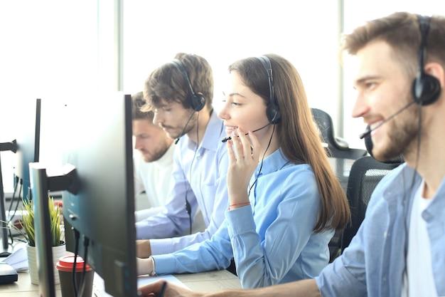 그녀의 팀과 함께 콜센터 직원의 초상화. 직장에서 웃는 고객 지원 담당자.