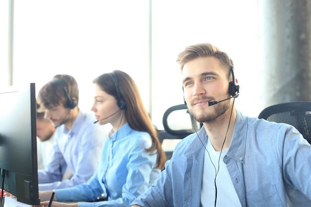 Портрет работника call-центра в сопровождении своей команды. улыбающийся оператор службы поддержки клиентов на работе.