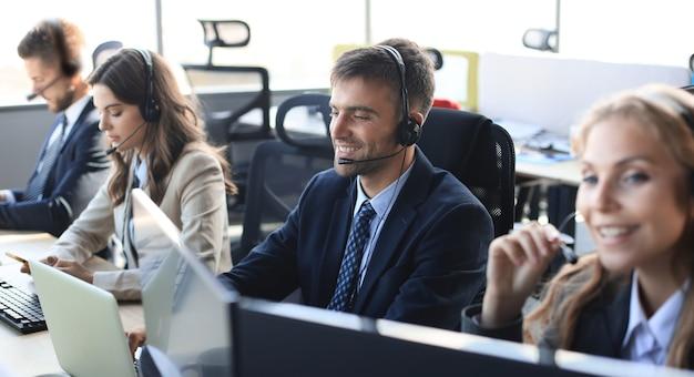 그의 팀과 함께 콜센터 직원의 초상화. 직장에서 웃는 고객 지원 담당자.