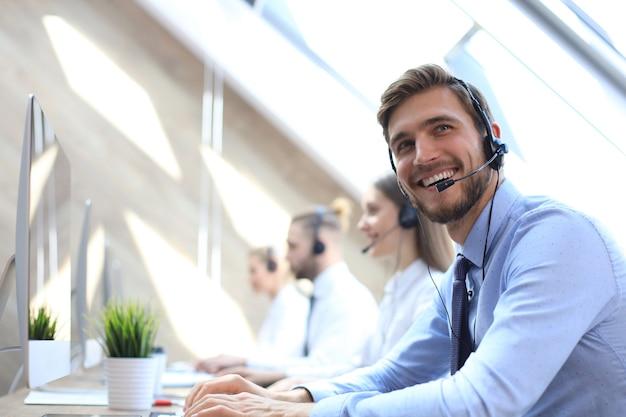 Портрет работника call-центра в сопровождении своей команды. улыбающийся оператор службы поддержки клиентов на работе. Premium Фотографии