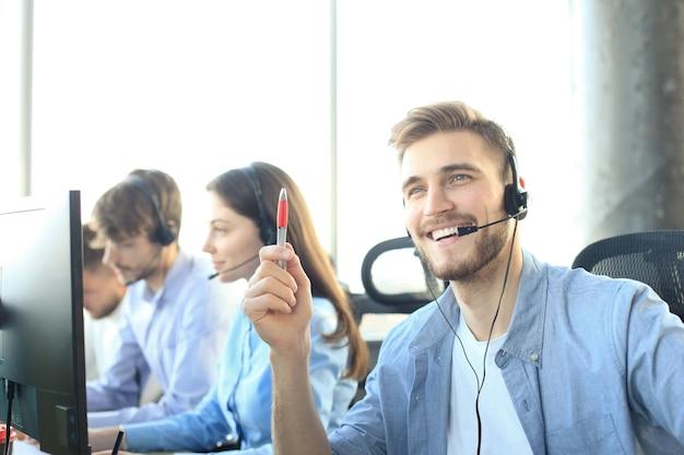 그의 팀과 함께 콜 센터 직원의 초상화. 직장에서 웃는 고객 지원 담당자.