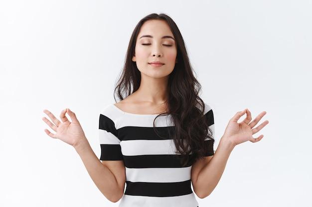 Портрет спокойной и радостной восточноазиатской женщины, которая сохраняет разум здоровым, расслабляется с помощью йоги или медитации, глубоко вздыхает и закрывает глаза, держится за руки боком со знаками мудра дзен, белый фон