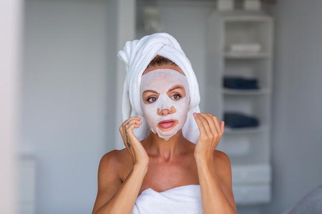 머리에 수건과 얼굴에 화장품 마스크와 진정 백인 예쁜 여자의 초상화 얼굴 피부 관리 개념 여성 집에서 침대에서 휴식