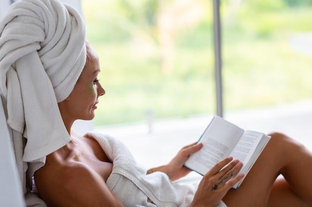 Портрет спокойной кавказской красивой женщины с полотенцем на голове и патчами маски для глаз на лице концепция ухода за кожей лица женщина расслабляется на кровати дома