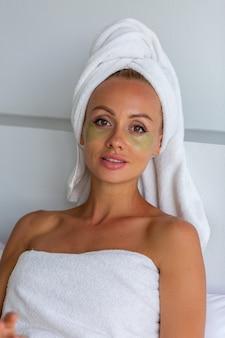 얼굴에 머리와 눈 마스크 패치에 수건으로 진정 백인 예쁜 여자의 초상화 얼굴 피부 관리 개념 여성 집에서 침대에서 휴식