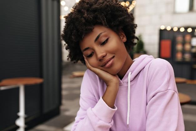 보라색 까마귀를 입은 차분하고 매력적인 갈색 곱슬머리 여성의 초상화는 밖에서 눈을 감고 부드럽게 웃고 있습니다.