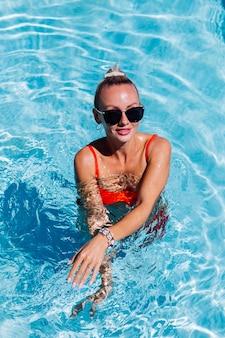 화창한 날에 파란색 수영장에서 검게 그을린 피부와 선글라스에 진정 행복한 여자의 초상화