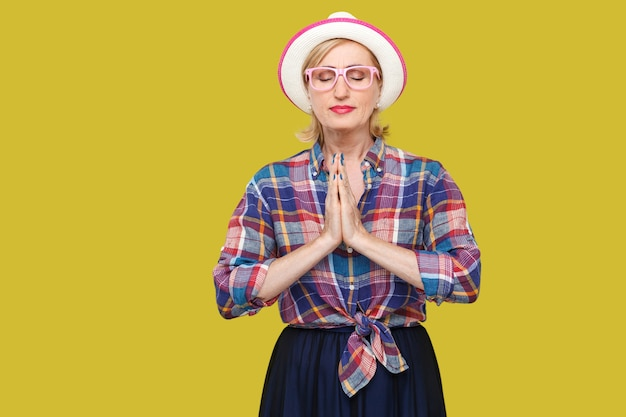 手のひらの手で立って、目を閉じて、ヨガのポーズの練習をしている帽子と眼鏡とカジュアルなスタイルで落ち着いたモダンでスタイリッシュな成熟した女性の肖像画。黄色の背景に分離された屋内スタジオショット。