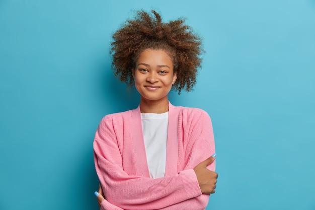 만족 한 표정으로 차분한 기분 좋은 외모의 여인의 초상화는 팔짱을 끼고 꼬리를 빗질 한 덥수룩 한 곱슬 머리를 즐겁게 듣고 친구가 누군가와 캐주얼 한 이야기를했습니다.