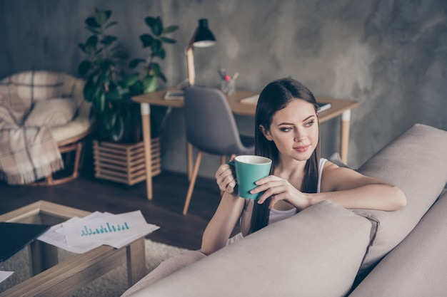 Портрет спокойной довольной девушки-менеджера пьет горячий кофе