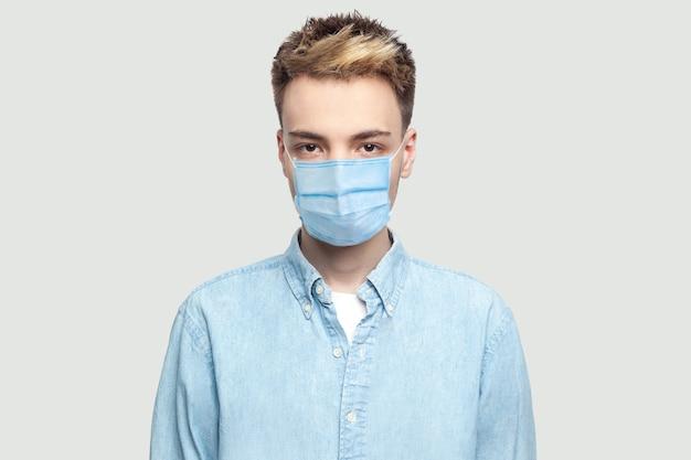 水色のシャツに立って真面目な顔でカメラを見ているサージカルマスクを持つ穏やかな深刻なハンサムな若い男の肖像画。灰色の背景のコピースペースで撮影された屋内スタジオ。
