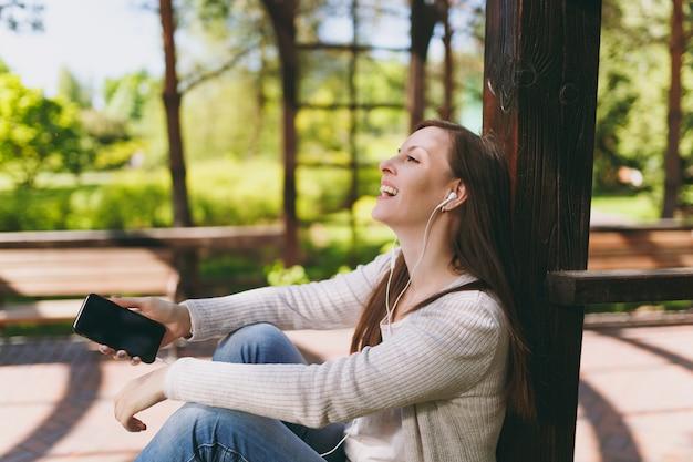 캐주얼 옷에 진정 여자의 초상화입니다. 야외 거리의 공원에 앉아 있는 여성은 빈 화면이 있는 휴대폰으로 음악을 듣고 이어폰의 공간을 복사합니다. 라이프 스타일 개념입니다.