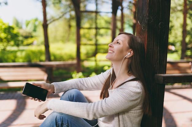 Портрет спокойной женщины в повседневной одежде. женщина сидит в парке на улице на открытом воздухе на природе, слушая музыку в мобильном телефоне с пустым пустым экраном, чтобы скопировать пространство в наушниках. концепция образа жизни. Premium Фотографии
