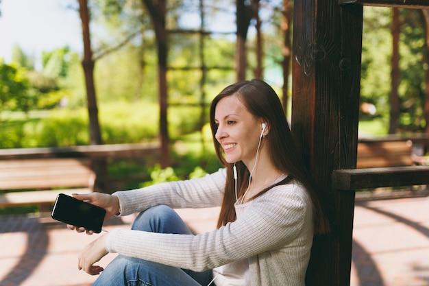 Портрет спокойной женщины в повседневной одежде. женщина сидит в парке на улице на открытом воздухе на природе, слушая музыку в мобильном телефоне с пустым пустым экраном, чтобы скопировать пространство в наушниках. концепция образа жизни.