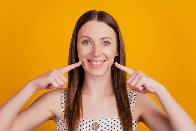 솔직하고 쾌활한 여성의 초상화는 완벽한 건강한 치아를 노란색 배경에 직접 손가락으로 보여줍니다.