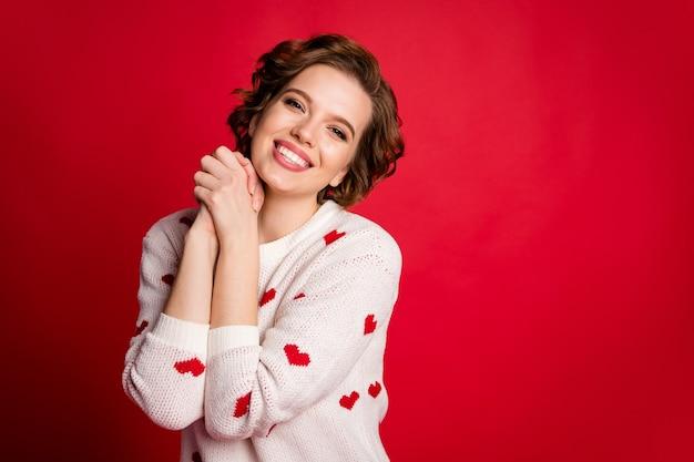 Портрет откровенной милой девушки-любовника скрестив руки в стильном модном джемпере, изолированном на красной стене