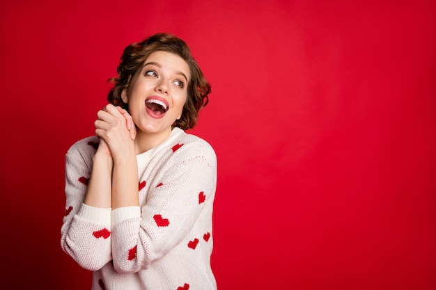 솔직한 사랑스러운 귀여운 소녀 애인 크로스 손의 초상화는 붉은 벽에 고립 된 세련된 유행 점퍼를 착용