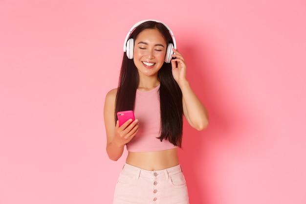 Портрет беззаботной привлекательной азиатской женщины, наслаждающейся любимой песней, закройте глаза, чтобы расслабиться, слушая музыку в наушниках, держа мобильный телефон и стоя на розовом фоне.