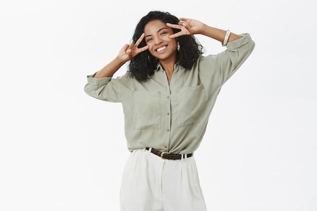 ブラウスとパンツでのんきな魅力的で明るい若いアフリカ系アメリカ人の成功した女性の肖像画