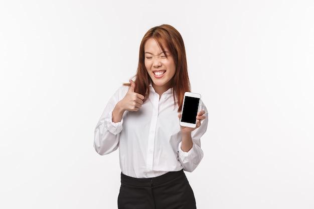 のんきな陽気で満足の笑みを浮かべてアジアの女性のシャツ、スカート、愚かな晴れやかなにやにや笑いで携帯電話のディスプレイを示すの肖像画のような親指を立てるか、白い壁に承認