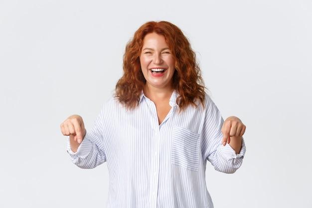 Портрет беззаботной веселой рыжей женщины смеясь и указывая пальцами вниз счастливыми. забавная красивая дама, женщина-предприниматель, показывая отличный бизнес-план, стоя у белой стены.