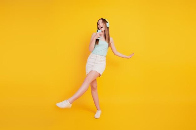 のんきな狂気の興奮した女性のダンスの肖像画は、黄色の背景で楽しんでください