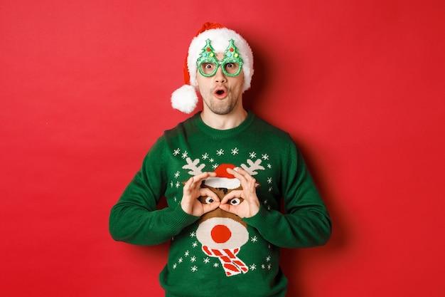 サンタの帽子とパーティーグラスでのんきなハンサムな男の肖像画、彼のクリスマスセーターをからかって、赤い背景の上で幸せそうに見える
