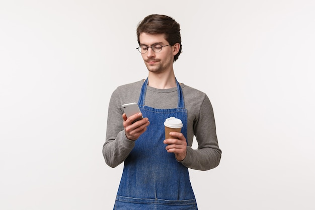 Портрет беззаботного красивого молодого студента, работающего неполный рабочий день в ресторане в фартуке, с перерывом на обед, с помощью мобильного телефона и пить кофе из чашки на вынос,