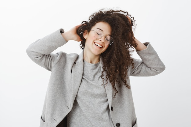 Портрет беззаботной счастливой эмоциональной женщины в сером пальто и очках, трогающей и размахивающей милыми вьющимися волосами, радостно улыбаясь с закрытыми глазами