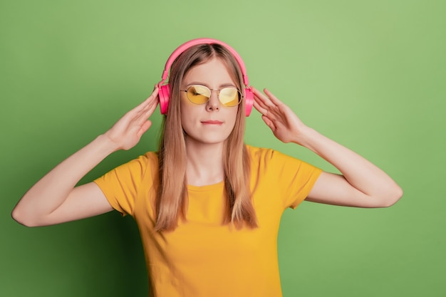 평온한 힙스터 여성의 초상화는 녹색 배경에 헤드폰 선글라스 노란색 티셔츠를 입고 음악을 듣는 것을 즐깁니다.