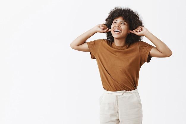 갈색 티셔츠에 평온한 무관심하고 행복한 젊은 아프리카 계 미국인 여자의 초상화는 검지 손가락으로 귀를 덮고 넓은 미소를 듣고 큰 소리로 즐겁게 올려다.