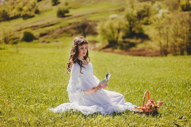Портрет беззаботной молодой женщины в белом винтажном свадебном платье в весенней садовой долине