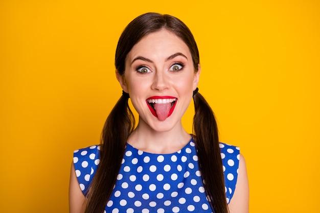 Портрет беззаботной глупой сумасшедшей девочки-подростка показывает язык, что ее подруга носит красивую одежду в горошек, изолированную на ярком цветном фоне