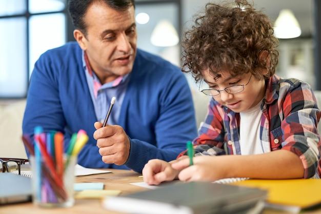 家の机に一緒に座っている間、彼の息子、学童と宿題を話し合って、助けている中年のラテン系の父親を気遣う肖像画。遠隔教育、家族、父性の概念