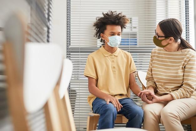 Портрет заботливой матери, утешающей сына, ожидая очереди в медицинской клинике для вакцинации, оба в масках, копировальное пространство